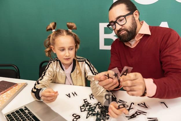 Quebra-cabeça de palavras. professor de cabelo escuro e barbudo usando óculos mostrando novas palavras para seu aluno