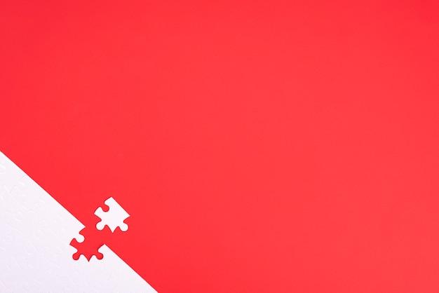 Quebra-cabeça de peças brancas sobre fundo vermelho, com lugar para o seu texto