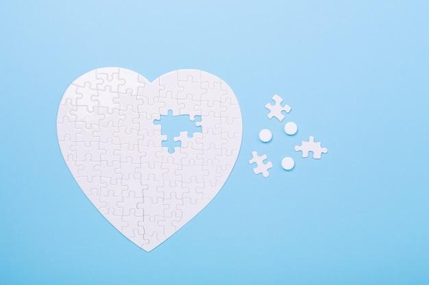 Quebra-cabeça em forma de coração e comprimidos brancos em azul