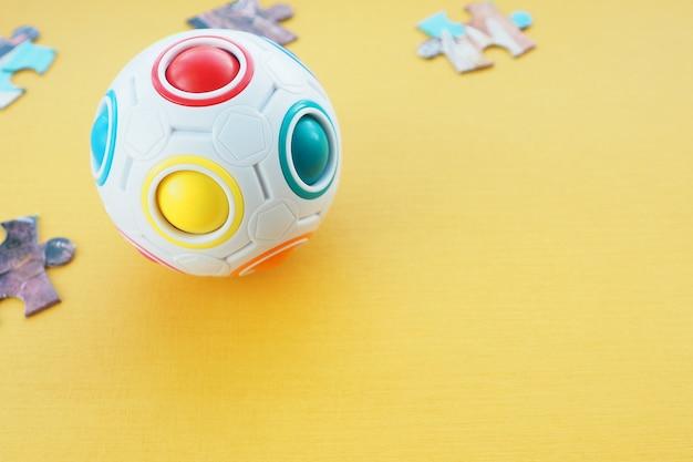 Quebra-cabeça infantil sob a forma de uma bola com bolas coloridas dentro e detalhes de um quebra-cabeça de papelão sobre um fundo amarelo. espaço para texto.