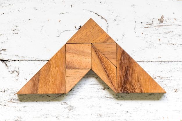 Quebra-cabeça tangram em forma de seta no antigo fundo de madeira branco