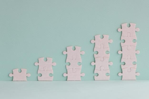Quebra-cabeças brancos em forma de conceito de pirâmides financeiras de torres crescentes