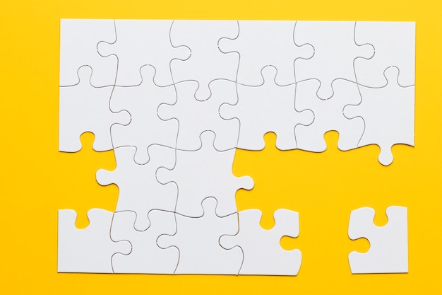 Quebra-cabeças de papelão branco sobre fundo amarelo