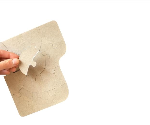 Quebra-cabeças de papelão nas mãos femininas, close-up.