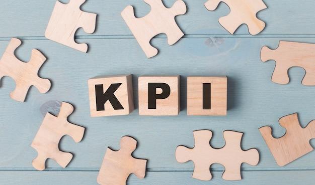 Quebra-cabeças em branco e cubos de madeira com o texto kpi mentem sobre um fundo azul claro.