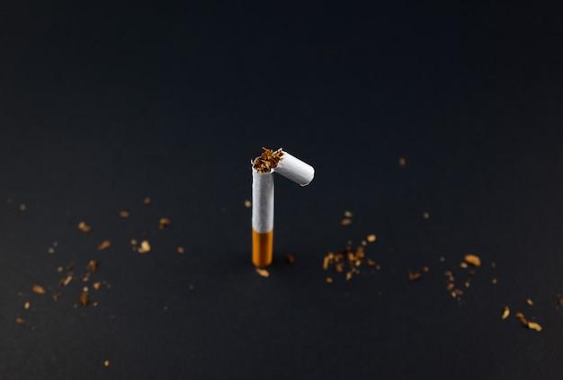 Quebra de cigarro tabaco para fumar em papel enrolado em fundo preto de textura grunge