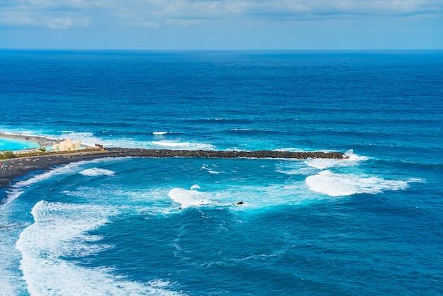 Quebra-mar de praia com areia preta. playa de martianez, porto da cruz, tenerife, espanha