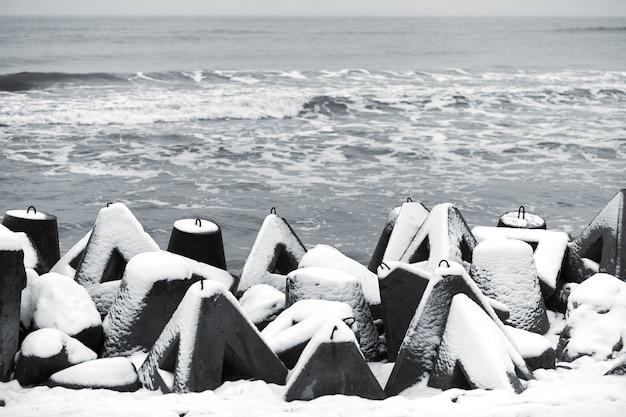 Quebra-mares de concreto cobertos de neve contra o mar de inverno. proteção costeira na neve