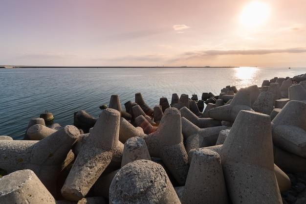 Quebra-mares de tetrapod na água do mar. bela paisagem do sol com tetrapodes de concreto