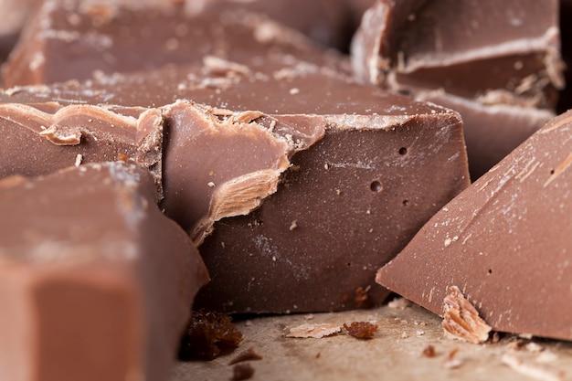Quebrado em várias partes pedaços de chocolate de cacau, alimento natural de cacau, açúcar, manteiga de cacau, pedaços grandes de chocolate verdadeiro natural
