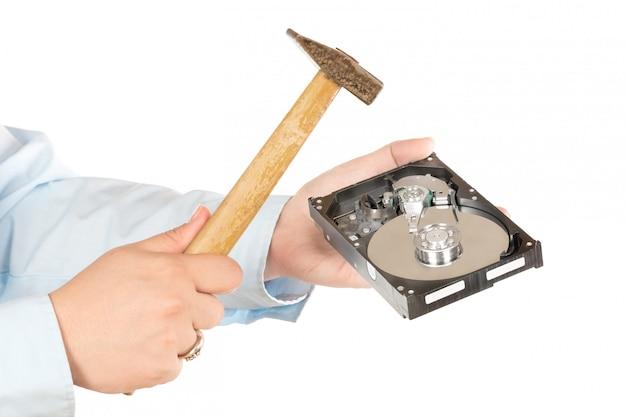 Quebrando a unidade de disco rígido com um martelo. isolado no branco