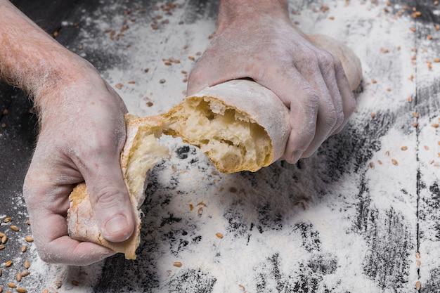 Quebrando pão fresco. conceito de cozimento e cozimento. mãos rasgando pão na mesa de madeira rústica polvilhada com farinha. mãos sujas e manchadas de padeiro. tonificação suave