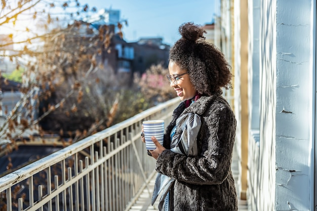 Quebre na varanda. mulher alegre e incomum com cabelo desleixado, bebendo uma bebida quente e ficando no frio do outono