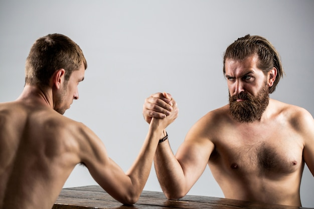 Queda de braço. homem barbudo fortemente musculoso lutando contra um homem fraco e franzino.