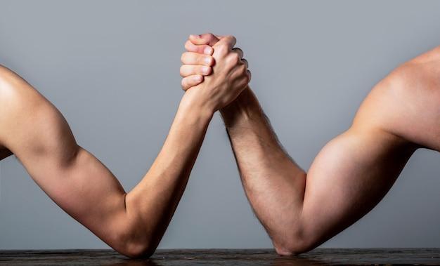 Queda de braço. homem fortemente musculoso lutando contra um homem fraco e franzino.