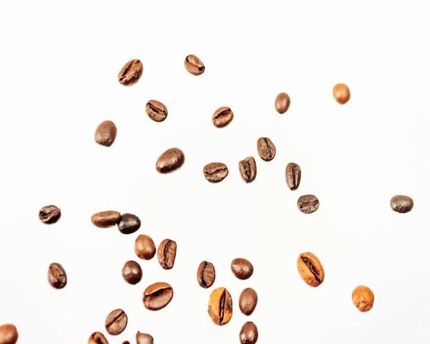 Queda de grãos de café isolados no fundo branco, traçado de recorte, profundidade total de campo. produto cerealífero. bebida quente. fechar-se. colheita. fundo natural. energia. voo, orientação horizontal