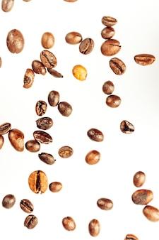 Queda de grãos de café isolados no fundo branco, traçado de recorte, profundidade total de campo. produto cerealífero. bebida quente. fechar-se. colheita. fundo natural. energia. voo, orientação vertical