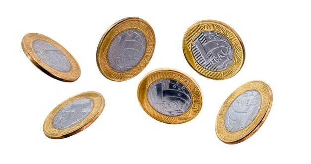 Queda de moedas de um real brasileiro isoladas na superfície branca.