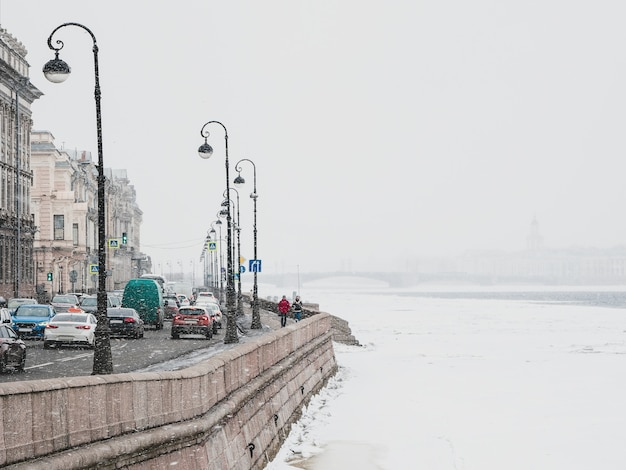 Queda de neve de foco suave. queda de neve da primavera em são petersburgo. engarrafamento na margem do rio neva. rússia.