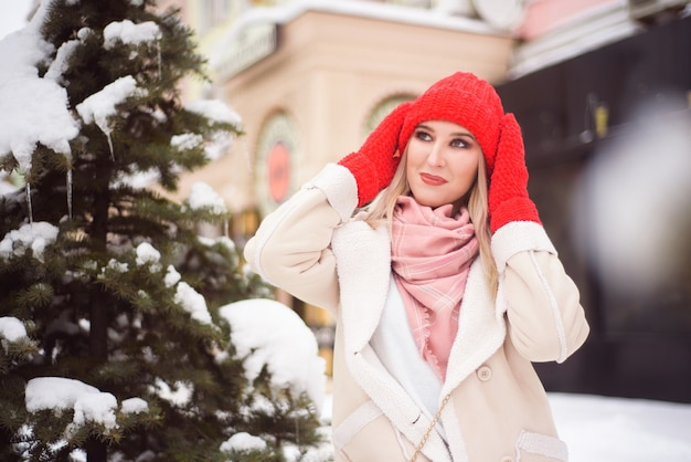 Queda de neve mulher cidade natal lá fora, retrato da cidade na neve, jovem modelo posando em olhar festivo.