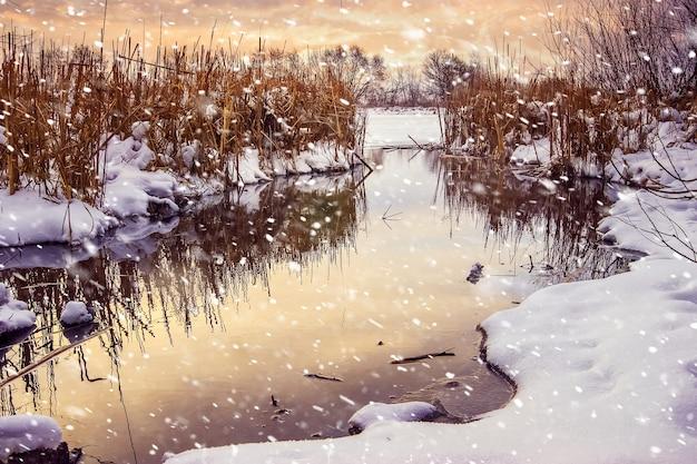 Queda de neve sobre o rio ao pôr do sol, vista de inverno