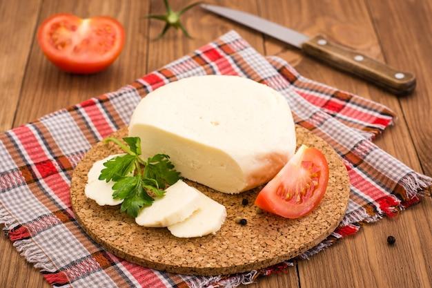 Queijo adyghe, tomate e salsa em um substrato