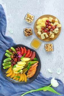 Queijo antipasto e pratos de frutas, várias nozes, mel, uvas