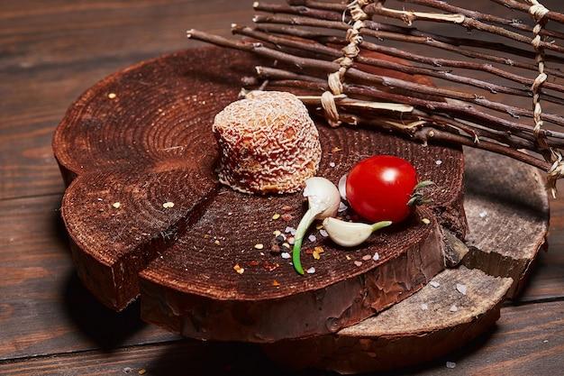 Queijo artesanal com tomate cereja e alho em uma cabana de madeira