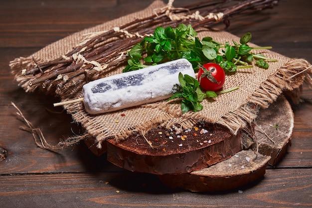 Queijo artesanal com tomate cereja e ervas em uma casa de toras de madeira