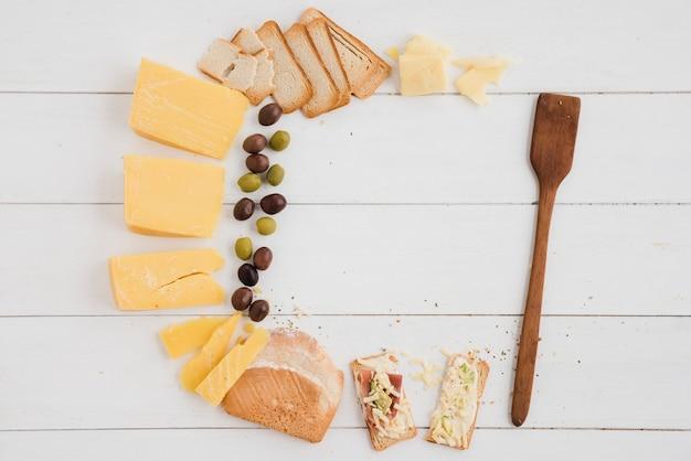 Queijo; azeitonas e pão para o café da manhã com espátula de madeira na mesa de prancha