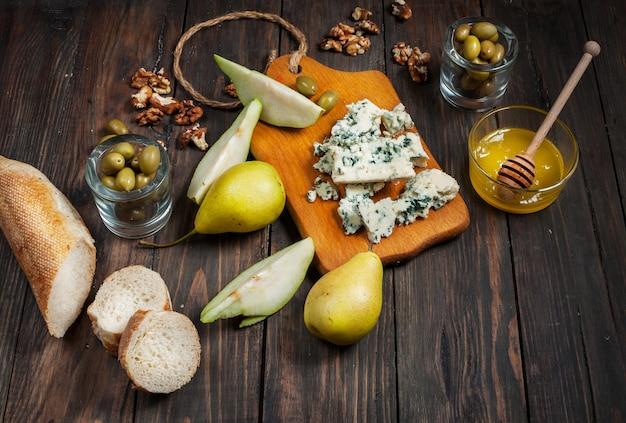 Queijo azul com mel, azeitona e peras na mesa rústica.