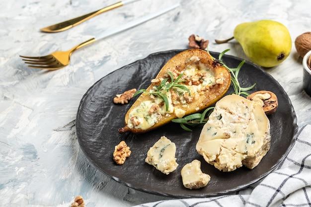 Queijo azul com peras e nozes. aperitivo com pêra assada com dorblu, gorgonzola, roquefort. conceito de deliciosa comida equilibrada.