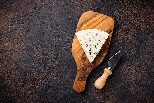 Queijo azul e faca na placa de corte