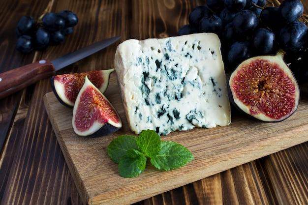Queijo azul e frutas na madeira marrom
