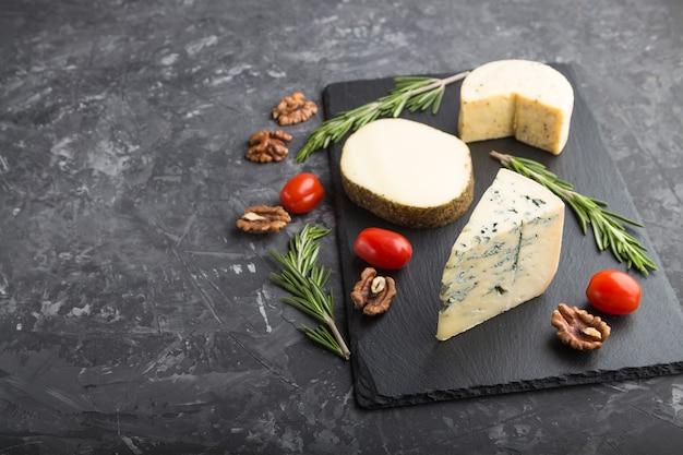 Queijo azul e vários tipos de queijo com alecrim e tomate em uma placa de ardósia preta em uma superfície de concreto preto