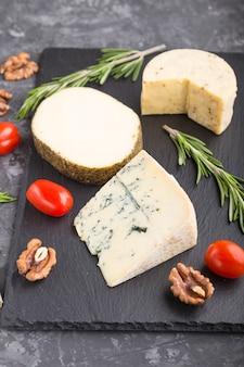 Queijo azul e vários tipos de queijo com alecrim e tomate na placa de ardósia preta sobre fundo preto de concreto.