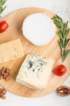 Queijo azul e vários tipos de queijo com alecrim e tomate na placa de madeira sobre uma superfície de madeira branca