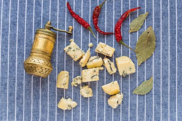 Queijo azul perto de pimenta vermelha seca e folhas
