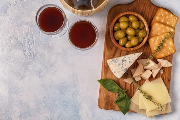 Queijo, biscoito, azeitonas na tábua e taças de vinho tinto