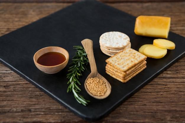 Queijo, bolachas, nacho chips e ervas de alecrim na placa de ardósia