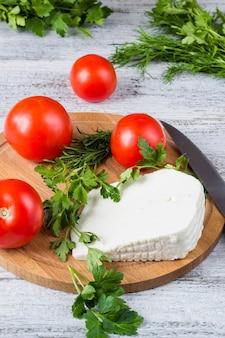 Queijo branco, faca, salsa, tomate em uma mesa de madeira