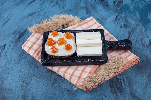 Queijo branco fatiado e pão com creme e geléia na tábua
