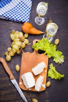 Queijo branco, uva e alface com vinho branco