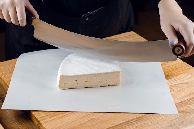 Queijo brie branco macio de leite de vaca. cortar o brie na mesa de madeira. comida orgânica deliciosa.