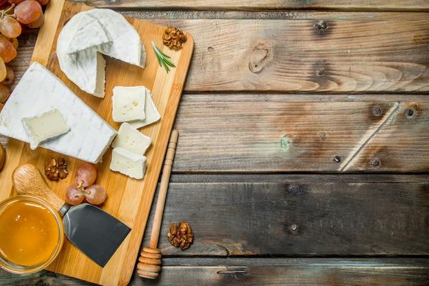 Queijo brie com uvas, nozes e mel a bordo na mesa de madeira.