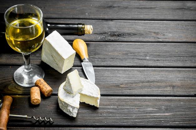 Queijo brie com vinho branco na mesa de madeira.