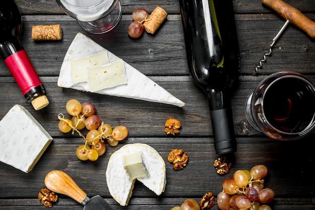 Queijo brie com vinho tinto, nozes e uvas na mesa de madeira.