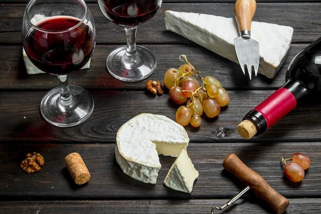 Queijo brie com vinho tinto, nozes e uvas. sobre um fundo de madeira.