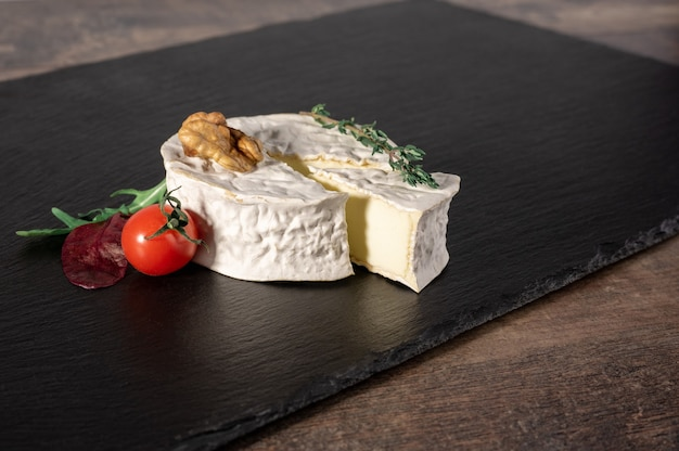 Queijo brie delicioso em fundo preto. tipo de queijo brie com noz e tomate