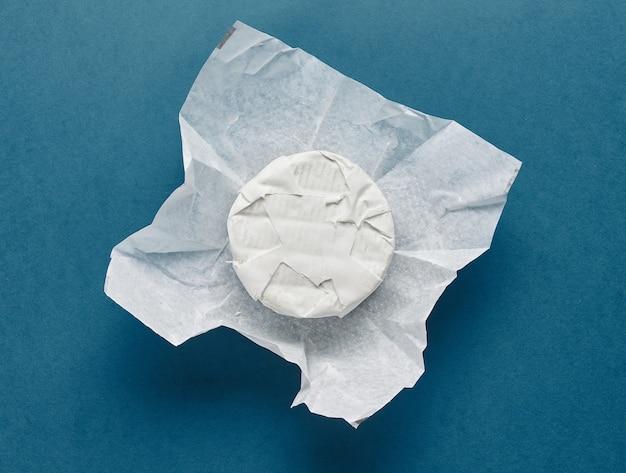 Queijo brie fresco em papel de embrulho no fundo de papel azul, vista superior